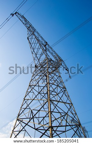 Electricity pylons and wires in a green field against blue sky.