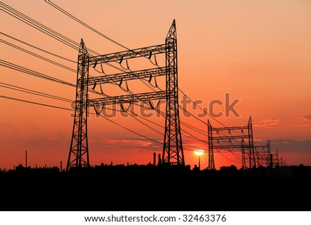 Electricity pylons at orange sunset - stock photo