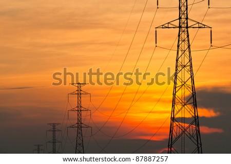 Electricity pylons at orange sunset - stock photo