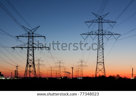 Electricity pylons at sunset near Brunsbüttel, Schleswig-Holstein, Germany. At the horizon chimneys and wind turbines. - stock photo