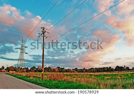 electricity pylons by a country road at dusk - stock photo