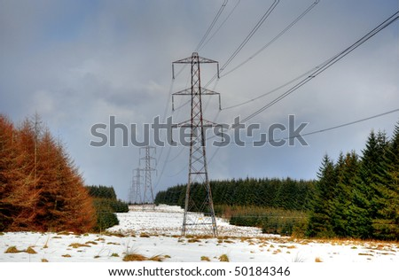 Electricity pylons disappearing into the distance - stock photo