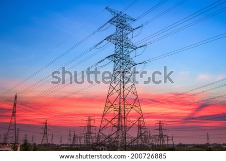 electricity pylons in transformer substation with a beautiful sunset sky  - stock photo