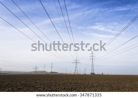 Electricity pylons leading from distribution power station blue cloudy sky background