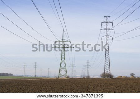 Electricity pylons leading from distribution power station blue cloudy sky background - stock photo