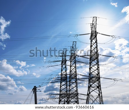 Electricity pylons on blue bright sky in sunshine - stock photo