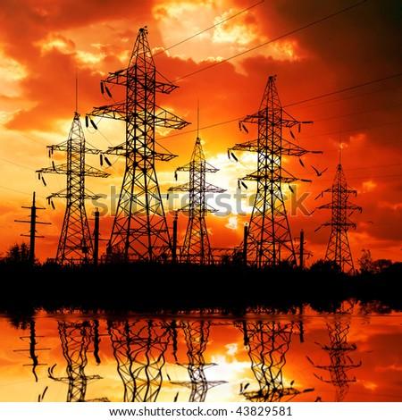 Electricity pylons on sunset background. - stock photo