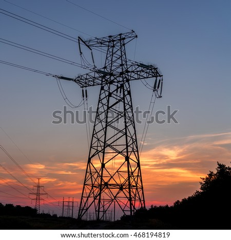 Electricity pylons, power lines sky at sunset.