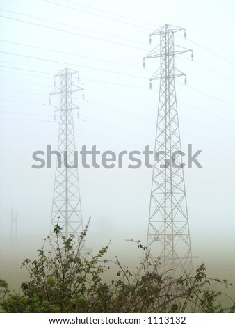 Electricity pylons/towers in heavy fog - stock photo