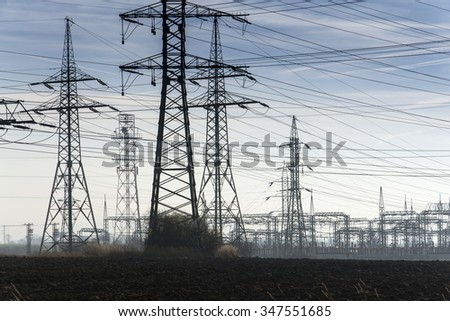 Electricity pylons with distribution power station blue cloudy sky - stock photo