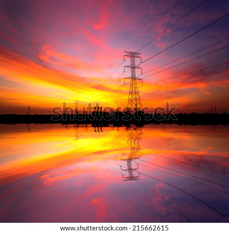 Electricity pylons with power plant at sunset - stock photo