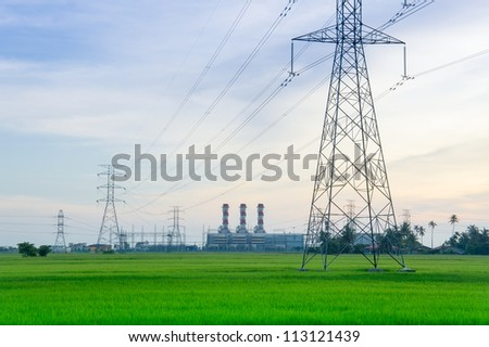 Electricity pylons with  power plant at the horizon - stock photo