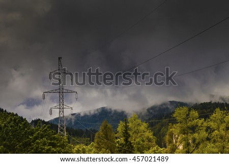 Electricity pylons with thunderstorm in background