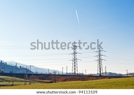 Electricity supply post in the green field - stock photo