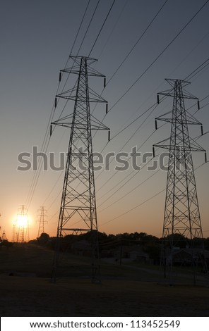 Electricity towers on the plains with sun rise in the background - stock photo