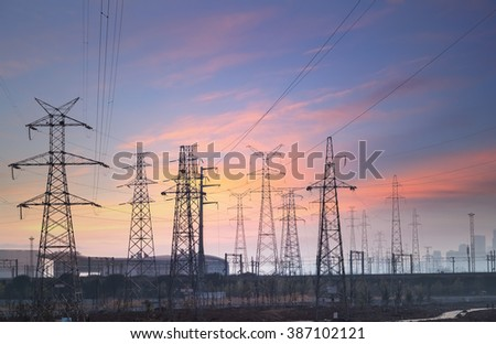 electricity transmission pylon at city suburb against the sunset glow sky