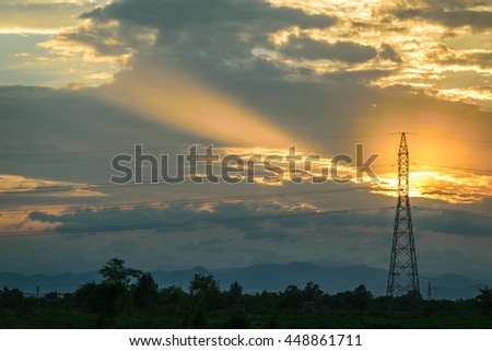 Electricity transmission pylon in cornfield or farm silhouetted  against the sunset background. - stock photo