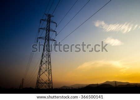 electricity transmission pylon silhouetted against blue and orange sky at dusk