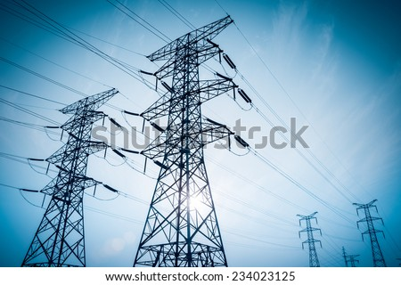 electricity transmission pylon silhouetted against blue sky at dusk  - stock photo