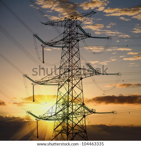 electricity transmission pylon silhouetted against sunset - stock photo