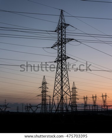 Electricity transmission pylon silhouetted against sunset sky. Electricity background.