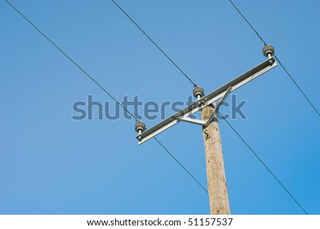 Electricity wire and wooden pole on blue sky - stock photo