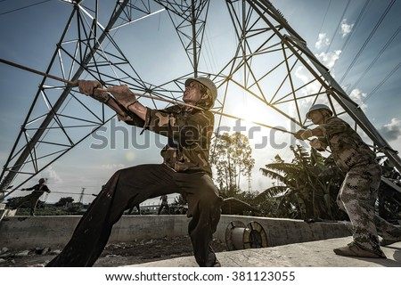 Electricity workers in erect high-voltage wire - stock photo