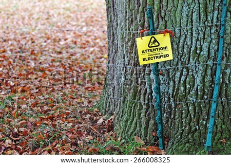 Electrified fencing with warning sign under a tree in a meadow.  - stock photo