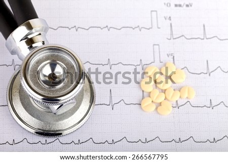 Electrocardiogram graph report with  heart shape pills on it - stock photo
