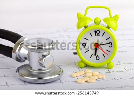 Electrocardiogram graph report with stethoscope and a clock on it - stock photo