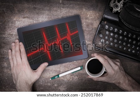 Electrocardiogram on a tablet - Concept of healthcare, heartbeat shown on monitor - red - stock photo