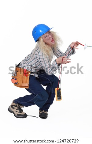 Electrocuted tradeswoman holding a multitester - stock photo