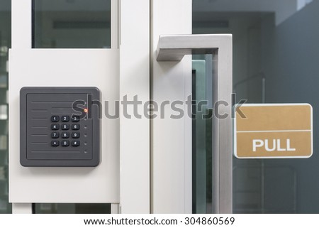 electronic access control door box with numeric keypad next to white aluminum frame glass door with sign - stock photo
