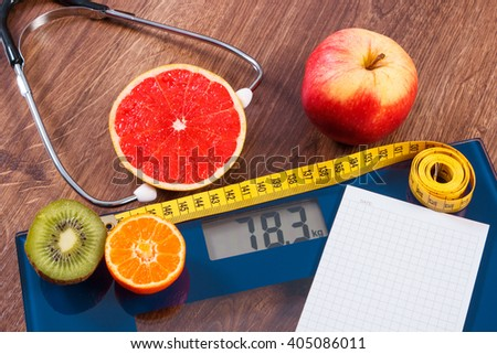 Electronic bathroom scale for weight of human body, tape measure and stethoscope with fruits, copy space for text on sheet of paper, healthcare, healthy lifestyles and slimming concept - stock photo