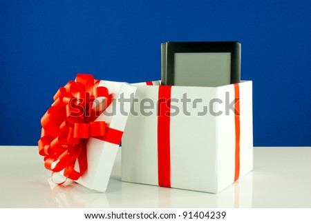 Electronic book reader in a box against blue background - stock photo