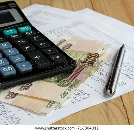 Electronic calculator, metal pen and Russian money on sheets of paper with numbers. Finance, Economics. Payment receipts, credit calculation.