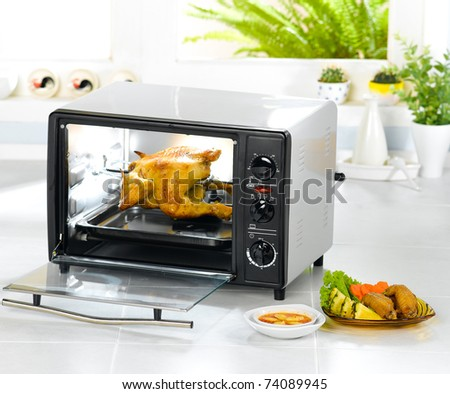 Electronic chicken roaster oven  fast convenience eatable and clean isolated in the kitchen interior  - stock photo