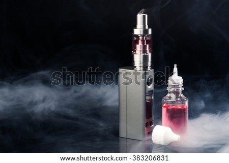 Electronic Cigarette and liquid at smoke on black background