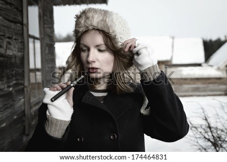 Electronic cigarette in hand sexy girl - stock photo