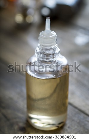 Electronic cigarette liquid flavour on wooden background, close up