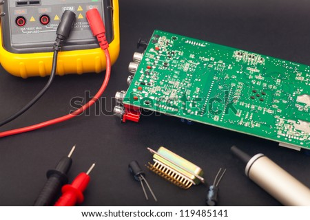Electronic circuit and polimeter in black background - stock photo