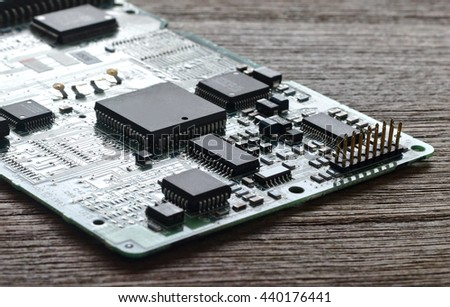 electronic circuit board with electronic components on wooden desk bakground. - stock photo