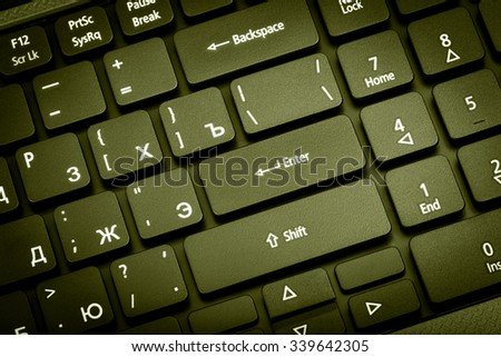 Electronic collection - close-up laptop keyboard with russian letter. The focus on the Enter key. Toning is green. - stock photo