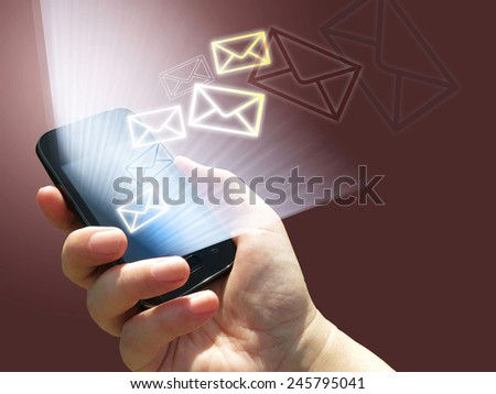 electronic communication - sending e-mails from mobile phone - hand holding a phone - stock photo
