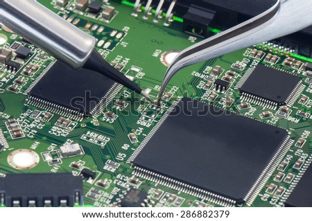Electronic component  held with tweezers by an engineer over a green motherboard. - stock photo