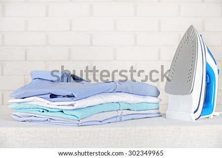 Electronic ironing and pile of clothes on board on brick wall background - stock photo