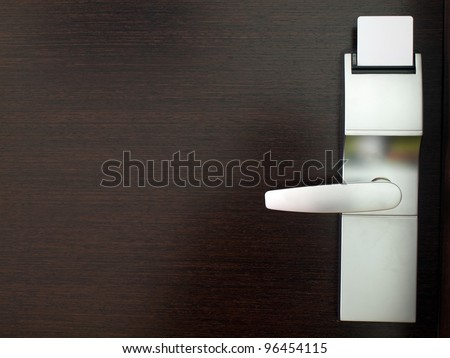 Electronic lock on door with white key card - stock photo