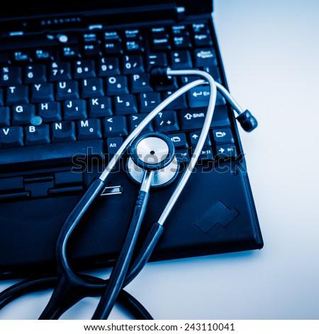 Electronic medical, stethoscope on PC/Laptop/Keyboard�¯�¼? blue toned images. - stock photo