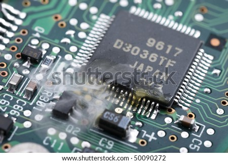 Electronic part malfunction, white smoke over the plate with chip. - stock photo