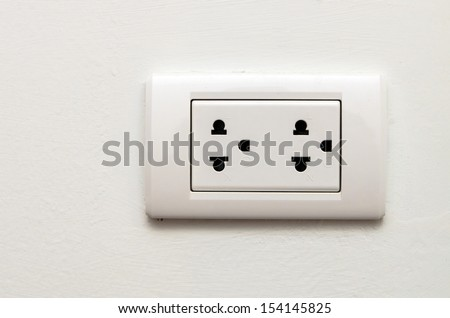 Electronic socket on white wall - stock photo